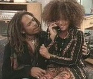 A Different World character Freddie Brooks sits in the Lap of her boyfriend Shazza Zulu in Afrocentric attire. They are both biracial and light skinned.