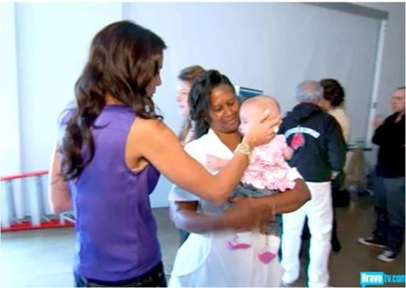 Black baby nurse Gina, holds baby Bryn as Mother Bethenny strokes Bryn's hair.