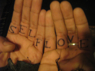 "Tattoo on inside of someone's fingers that says ""self love"""