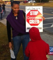 Sheri Davis-Faulkner at a Walmart Action with a Stop Corporate Greed Sign and her son